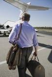 Älterer Geschäftsmann Walking Towards Airplane Lizenzfreies Stockfoto