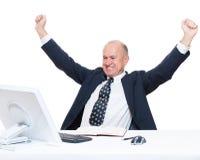 Älterer glücklicher Geschäftsmann, der an Arbeitsplatz sitzt Stockfoto