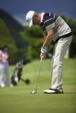 Älterer Golfspieler, der am Loch sich setzt. Lizenzfreies Stockfoto