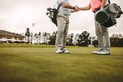 Älterer Golfspielerhändedruck am Golfplatz stockfotografie