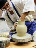 Älterer Handwerker spinnt Tonwaren auf seinem Rad an der Handwerks-Messe in Bratislava stockbilder
