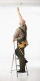 Älterer Heimwerker, der die Decke malt Lizenzfreie Stockfotos