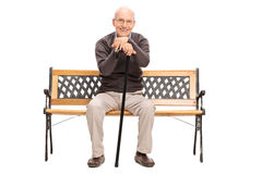 Älterer Herr, der auf einer Holzbank sitzt Stockbild