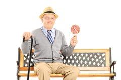 Älterer Herr, der auf einer Holzbank sitzt und ein colorfu hält Lizenzfreies Stockfoto