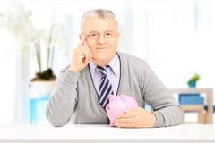 Älterer Herr, der auf einer Tabelle mit Sparschwein aufwirft Lizenzfreie Stockbilder