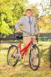 Älterer Herr, der ein Fahrrad in einem Park drückt Stockbild