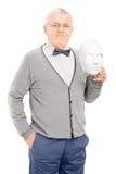 Älterer Herr, der eine Theatermaske hält Stockbilder