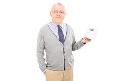 Älterer Herr, der eine Toilettenpapierrolle hält Stockfoto