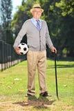 Älterer Herr, der einen Fußball im Park hält Stockfotografie