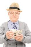 Älterer Herr, der Geld zählt Stockbild