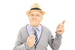 Älterer Herr, der Mikrofon hält und oben mit dem Finger zeigt Stockbilder