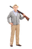 Älterer Herr, der mit einem Gewehr aufwirft Stockfotografie