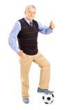 Älterer Herr mit dem Ball, der Daumen aufgibt Stockfoto