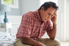 Älterer hispanischer Mann, der auf dem Bett leidet mit Krise sitzt stockfoto