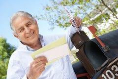 Älterer hispanischer Mann, der Briefkasten überprüft Lizenzfreie Stockbilder