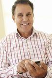 Älterer hispanischer Mann, der Smartphone verwendet lizenzfreie stockfotografie