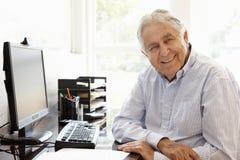 Älterer hispanischer Mann, der zu Hause an Computer arbeitet lizenzfreie stockbilder