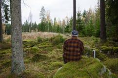 Älterer Holzfäller, der in einem Wald sitzt Lizenzfreie Stockfotografie