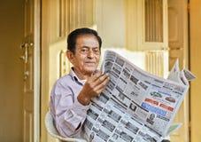 Älterer indischer Herr, der lokales Zeitungspapier liest stockbilder