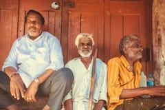 Älterer indischer Mann drei, der letzte Holztür im Freien des Stadtmarktes sitzt Lizenzfreies Stockbild