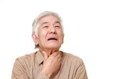 Älterer japanischer Mann, der die Kehlschmerz hat Stockfoto