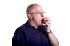 Älterer kahler Kerl in den Gläsern einen Pfirsich essend Stockfotos