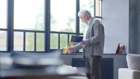 Älterer kaukasischer Mann, der ein Buch liest und einen köstlichen Tee in einer modernen Wohnung trinkt stock footage