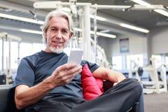 Älterer kaukasischer Mann an der Turnhalle, sein Telefon überprüfend Stockfotos