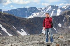 Älterer kaukasischer Wanderer mit Rucksack sprechend auf Mobiltelefon in den Bergen, Kopienraum Lizenzfreies Stockbild