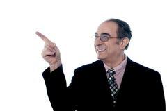 Älterer lächelnder Direktor, der weg zeigt lizenzfreie stockfotos
