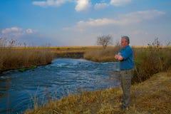 Älterer Landwirt, der über einem Fluss schaut Stockfotos