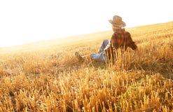 Älterer Landwirt, der auf einem Weizengebiet sitzt Lizenzfreie Stockfotografie