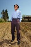Älterer Landwirt, der im Freien steht Stockfoto