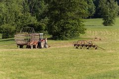 älterer Landwirt, der mit einem alten Traktor heut Lizenzfreie Stockfotos