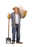 Älterer Landwirt, der mit einem Sack und einer Schaufel aufwirft Lizenzfreie Stockfotografie