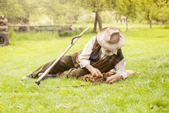Älterer Landwirt mit Sense Stockfotos