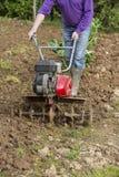 Älterer Landwirtgärtner, der im Garten mit rototiller, Pflügertraktor, cutivator, miiling Maschine arbeitet Lizenzfreies Stockfoto