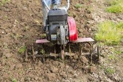 Älterer Landwirtgärtner, der im Garten mit rototiller, Pflügertraktor, cutivator, miiling Maschine arbeitet Stockfotos