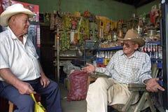Älterer Lebensmittelhändler, der mit Kundeninnerespeicher spricht Lizenzfreie Stockfotografie