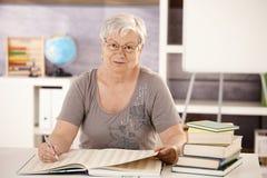 Älterer Lehrer in der Schule, die in einem Buch sucht stockbilder