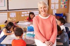Älterer Lehrer im Klassenzimmer mit Volksschule scherzt stockfotografie