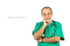 Älterer männlicher Chirurgiebetreiberdoktor mit grüner Uniformstellung lokalisiert auf Weiß Stockfotos