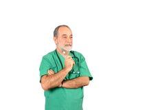 Älterer männlicher Chirurgiebetreiberdoktor mit grüner Uniformstellung lokalisiert auf weißem Hintergrund Stockfotografie