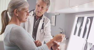 Älterer männlicher Doktor, der das zerbrochene Handgelenk des Patienten festsetzt lizenzfreie stockfotografie