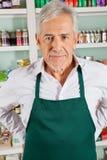 Älterer männlicher Inhaber, der im Gemischtwarenladen steht Stockfotografie