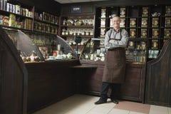 Älterer männlicher Inhaber, der im Shop steht Stockbild