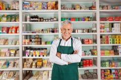 Älterer männlicher Inhaber, der im Supermarkt steht Stockbild