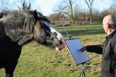 Älterer männlicher Künstler, der ein Pferd skizziert. Stockbild