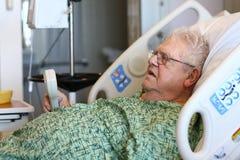Älterer männlicher Krankenhauspatient hält Fernsehapparat entfernt an Stockfotos