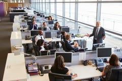 Älterer männlicher Manager, welche zu Arbeitskräften im Bürogroßraum spricht Lizenzfreie Stockfotos